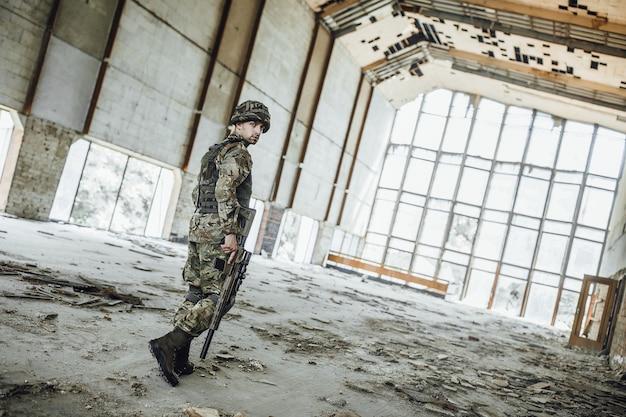軍事偵察作戦。手に大きなライフルを持った若い兵士が、後ろから見た崩壊した建物を通り抜けます!