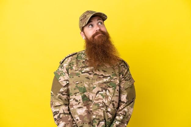 Военный рыжий мужчина изолирован на желтом фоне и смотрит вверх