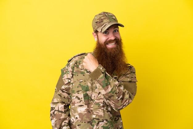 Военный рыжий человек над изолированным на желтом фоне празднует победу