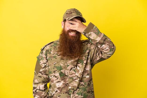 Военный рыжий мужчина изолирован на желтом фоне, закрывая глаза руками и улыбаясь