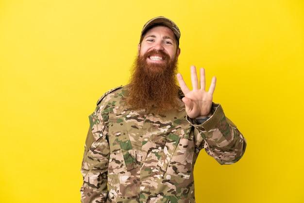 Военный рыжий человек над изолированным на желтом фоне счастлив и считает четыре пальцами
