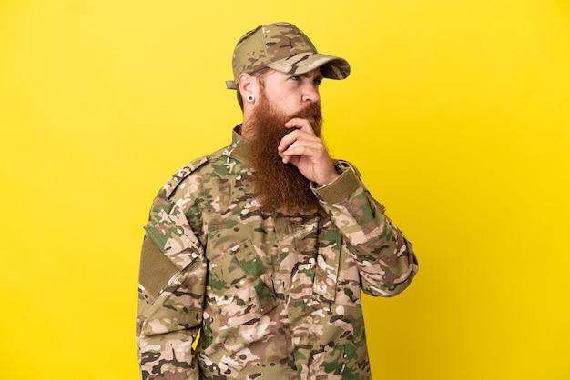 Военный рыжий мужчина изолирован на желтом фоне с сомнениями и смущенным выражением лица