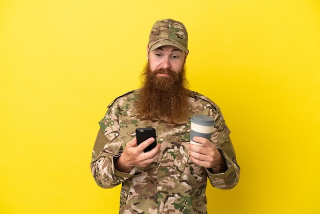 Военный рыжий мужчина на желтом фоне держит кофе на вынос и мобильный