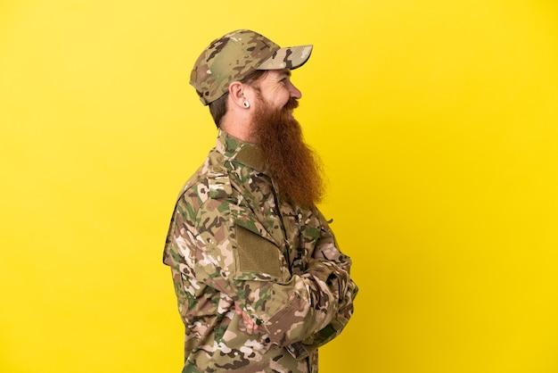 Военный рыжий мужчина над изолированным на желтом фоне в боковом положении