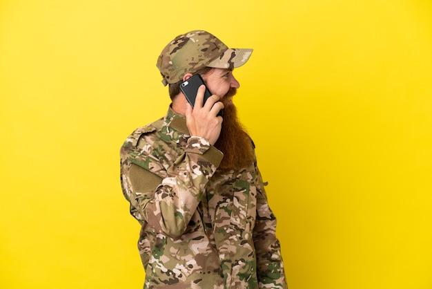 Военный рыжий мужчина изолирован на желтом фоне, разговаривая с кем-то по мобильному телефону