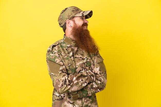 Военный рыжий человек над изолированным на желтом фоне смотрит сторону