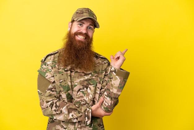 Военный рыжий мужчина изолирован на желтом фоне, указывая пальцем в сторону