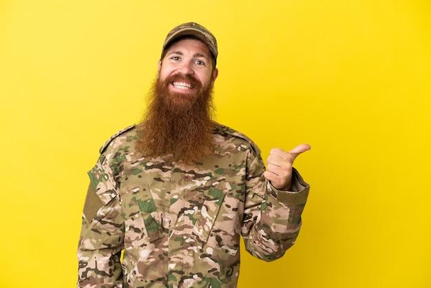 Военный рыжий мужчина изолирован на желтом фоне, указывая в сторону, чтобы представить продукт