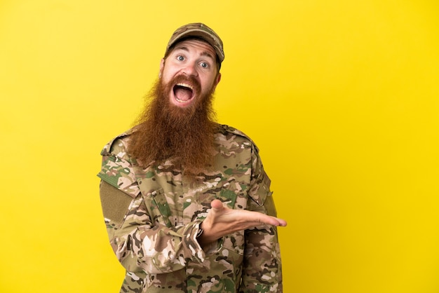 Военный рыжий мужчина изолирован на желтом фоне, представляя идею, улыбаясь в сторону
