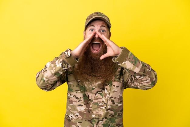 Военный рыжий мужчина над изолированным на желтом фоне кричит и что-то объявляет