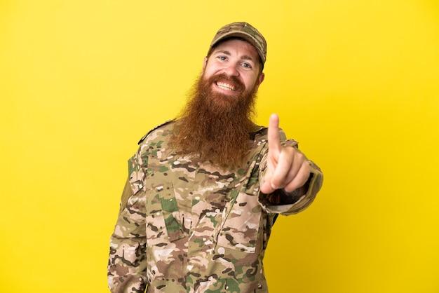 Военный рыжий мужчина изолирован на желтом фоне, показывая и поднимая палец