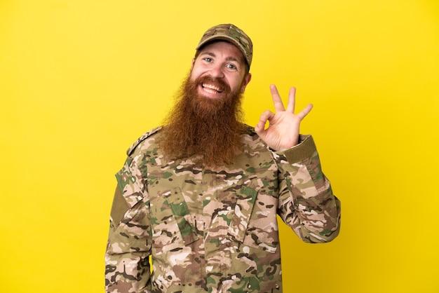 Военный рыжий мужчина изолирован на желтом фоне, показывая пальцами знак ок