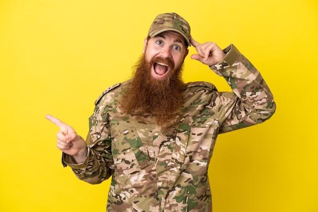 黄色の背景に孤立した軍の赤毛の男は驚いて、人差し指を横に向ける