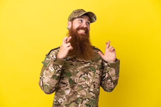 Военный рыжий мужчина изолирован на желтом фоне со скрещенными пальцами