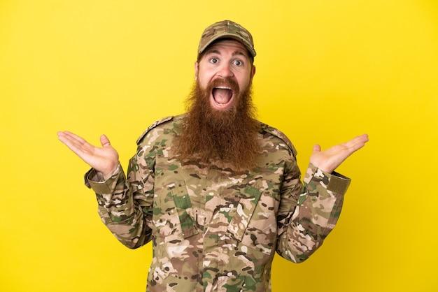 Военный рыжий мужчина изолирован на желтом фоне с шокированным выражением лица