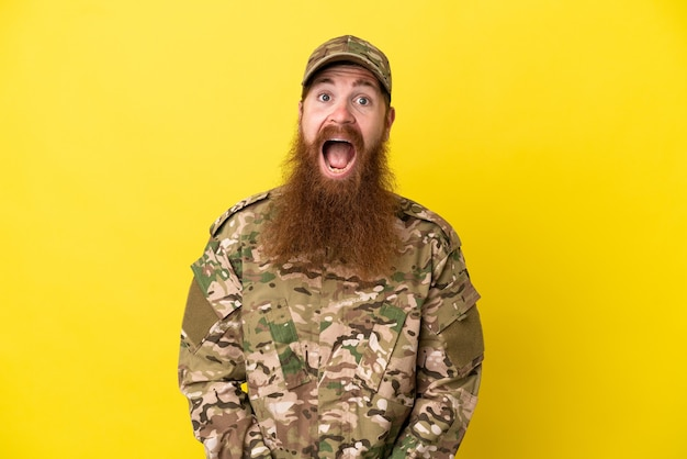 Военный рыжий мужчина изолирован на желтом фоне с удивленным выражением лица