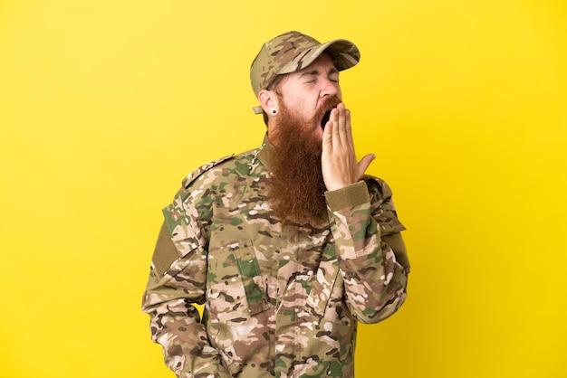 Военный рыжий мужчина изолирован на желтом фоне, зевая и прикрывая широко открытый рот рукой