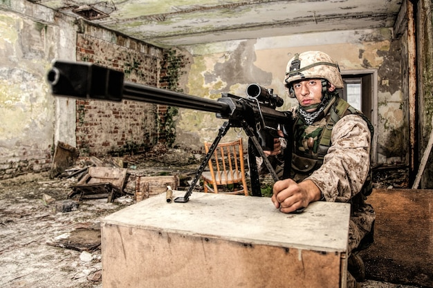 Military sniper armed with 50 caliber, anti-materiel sniper rifle on bipod, shooting from firing position in ruined, abandoned city building. urban warfare and guerrilla, war in city environment