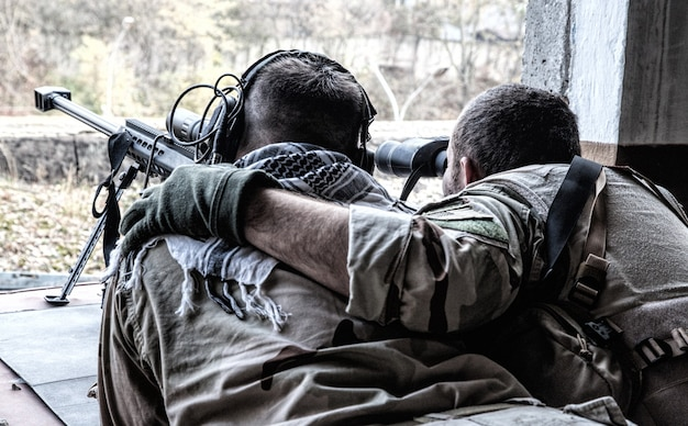 군사 저격수 팀 정찰병 전장 관찰, 쌍안경으로 목표물 수색, 저격수 어깨에 팔 잡기, 숨겨진 위치에서 대물 저격 소총으로 저격 사격 수정