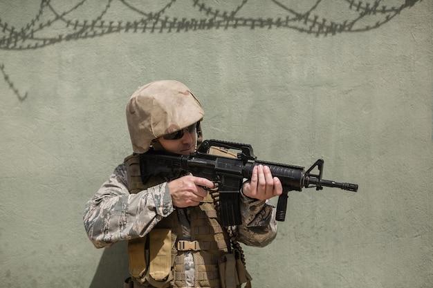 ブートキャンプでコンクリートの壁にライフルで狙いを定めている軍の兵士
