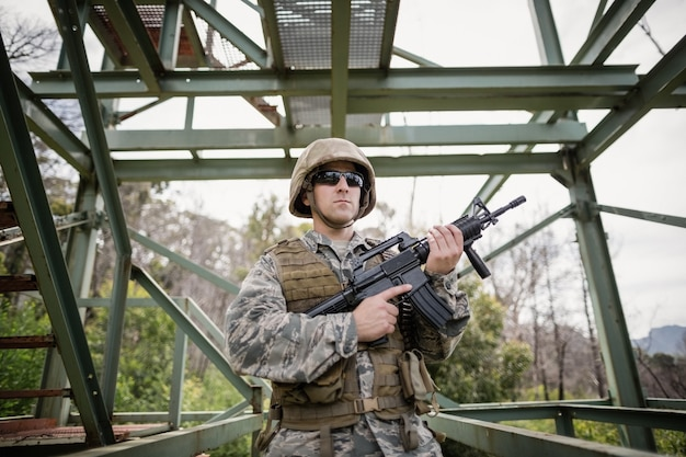Military soldier guarding with a rifle in boot camp