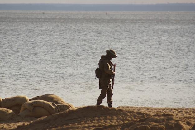 Военный солдат на пляже у кромки воды