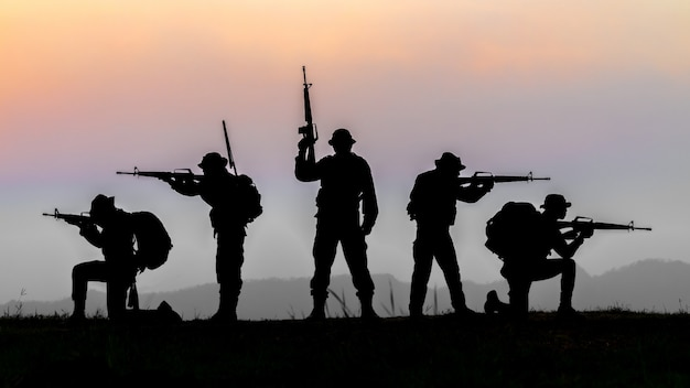Military or soldier silhouettes on sunset sky background, fully equipped and armed soldier standing on silhouettes environment in sunset.
