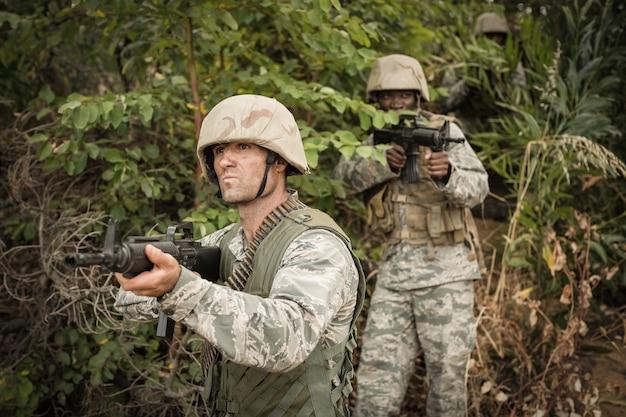 Военные солдаты во время учений с оружием в учебном лагере