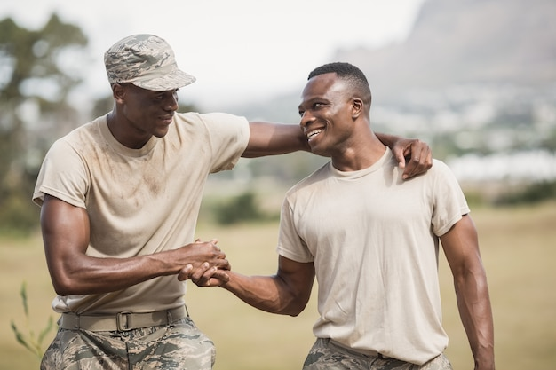 Military soldiers shaking hands during obstacle course in boot camp