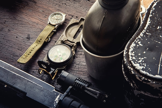 Military tactical equipment for the departure. assortment of survival hiking gear on wooden background