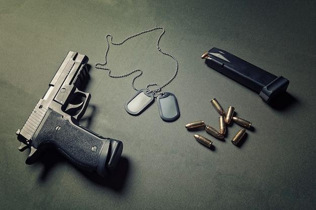 ミリタリートークン、ピストル、弾薬は緑の背景にあります。戦争、独立、堕落した兵士の記憶の概念。