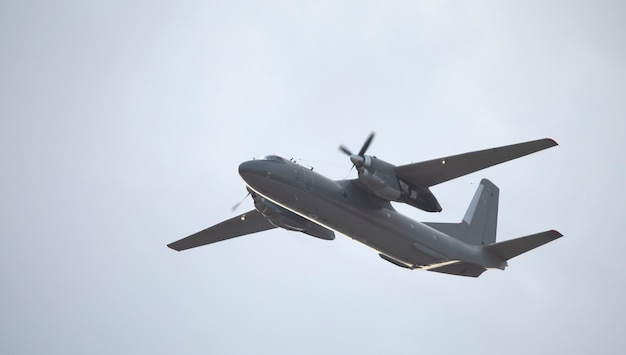 Military twin-engine transport aircraft on sky background.