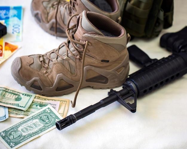 軍服と装備。白い背景に米ドル紙幣を備えたモダンな自動ハイパワーライフルとブーツ。アサルトブラックライフル銃口。犯罪、マフィア、テロ。セレクティブフォーカス Premium写真