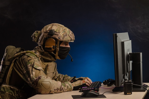 The military in uniform sitting at a computer conducts cyber warfare