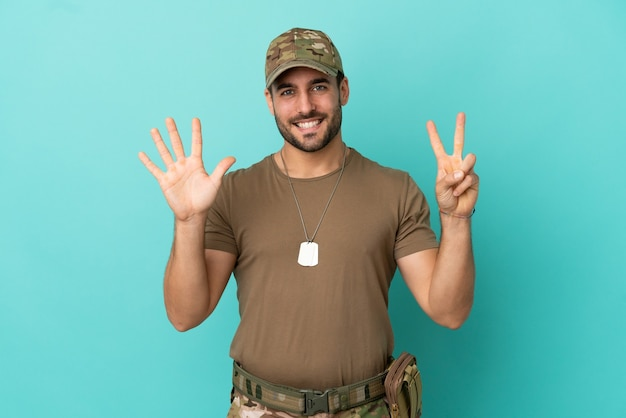 Military with dog tag over isolated on blue background counting seven with fingers