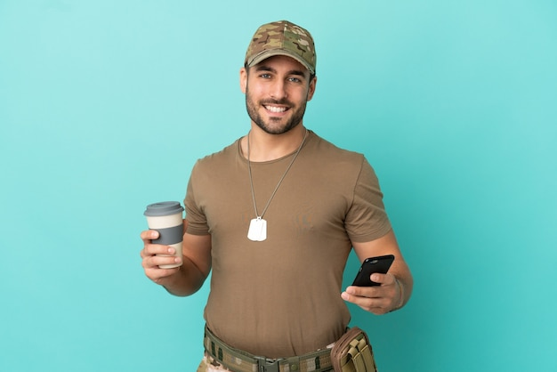 Military with dog tag over isolated on blue background holding coffee to take away and a mobile