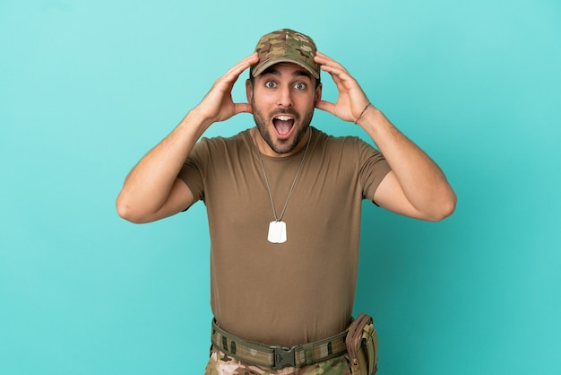 Military with dog tag over isolated on blue background with surprise expression