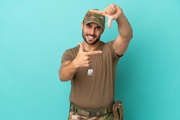 Военные с биркой собаки над изолированной на синем фоне фокусируя лицо. обрамление символа