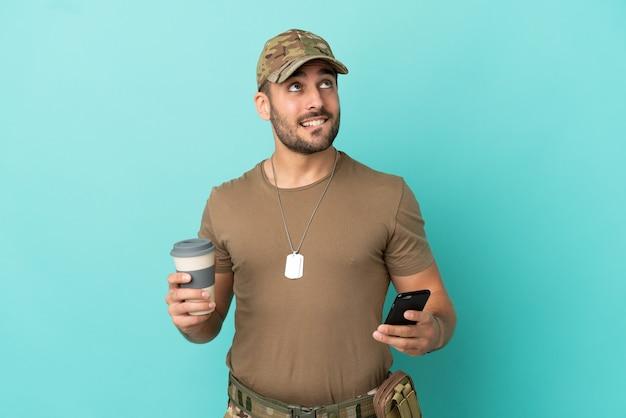 Военные с собачьей биркой на синем фоне, держа кофе на вынос и мобильный, думая о чем-то