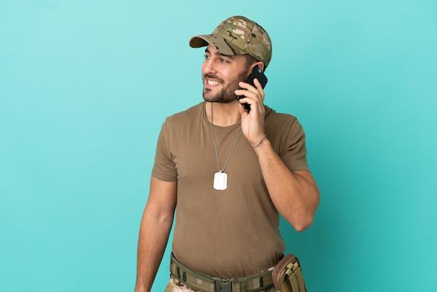 Военные с собачьей биркой на синем фоне, разговаривая с кем-то по мобильному телефону