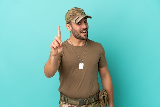Военные с собачьей биркой над изолированной на синем фоне, показывая и поднимая палец