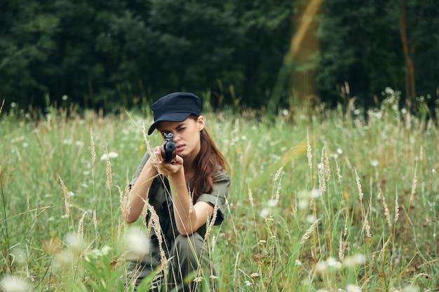 Военная женщина стоящая на коленях женщина целится из оружия