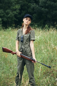 Military woman gun in hand hunting lifestyle travel fresh air green trees on background
