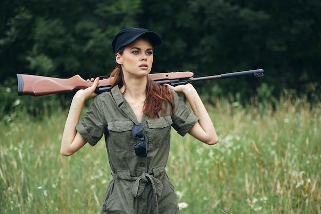 Военная женщина держит оружие за спиной черная кепка охотничий образ жизни зеленый комбинезон