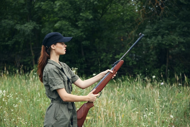 Military woman holding a gun in hand is a lifestyle fresh air green trees on background