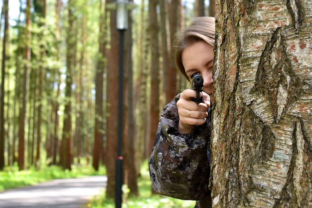Military woman shoots with a gun in  forest. hunter girl hiding behind a tree with weapons.
