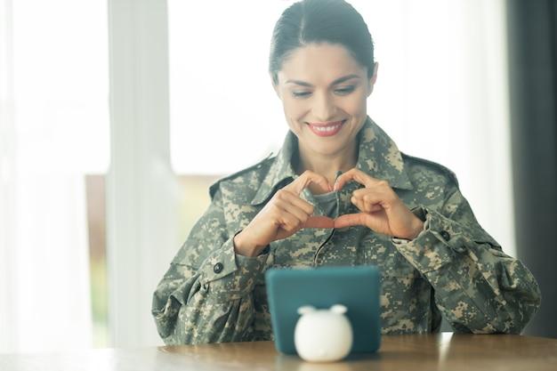 軍の女性の笑顔。家族にすべての彼女の愛を示し、ビデオチャットをしながら笑っている美しい軍の女性