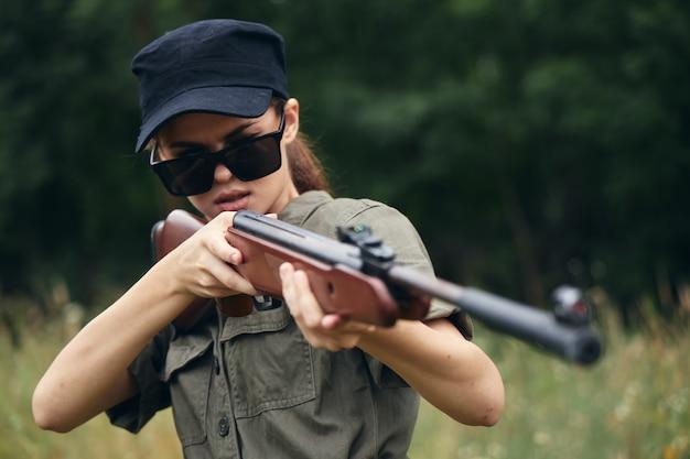 Военная женщина оружие в руке целится в охотничьи солнцезащитные очки с зелеными листьями