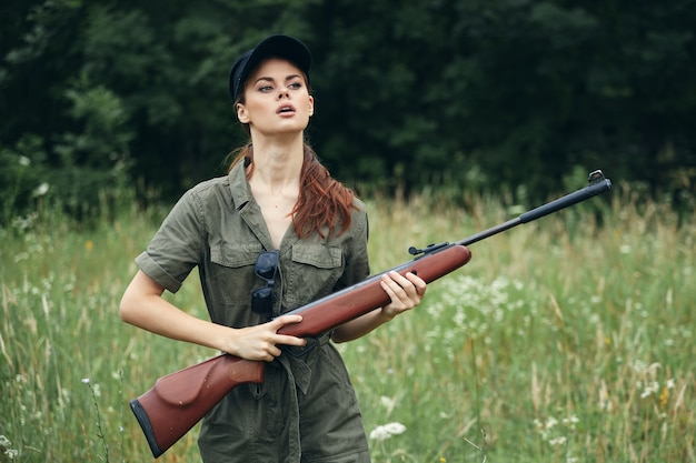 Military woman with weapons in hand, a green jumpsuit looks to the side black cap forest background