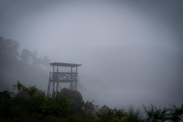 Военные деревянная сторожевая башня в джунглях, окруженных мистическим туманом. опасная концепция.